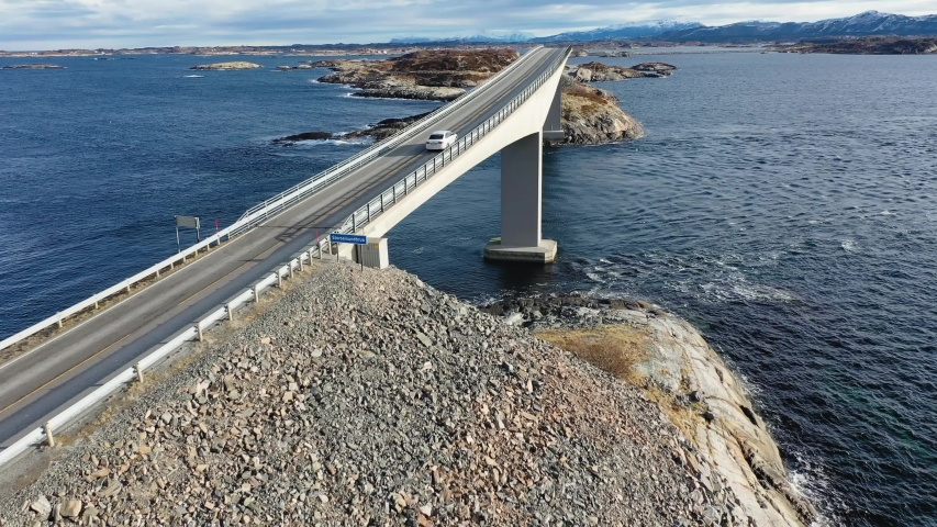 Winter atlantic road in Norway. Aerial view from a bird's flight. Car driving on the Strozandez bridge