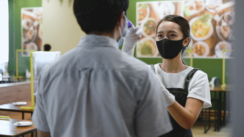 Asian staff restaurant waitress wear protective face mask scan customer temperature by thermometer before entering the restaurant to protect infection from flu fever and coronavirus covid-19 Royalty-Free Stock Footage #1052816945