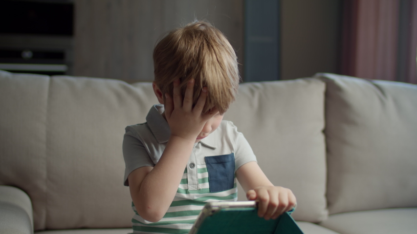 Preschool boy using tablet computer for online education sitting on couch at home. Kid using application to study online. Child with gadget. | Shutterstock HD Video #1052818760