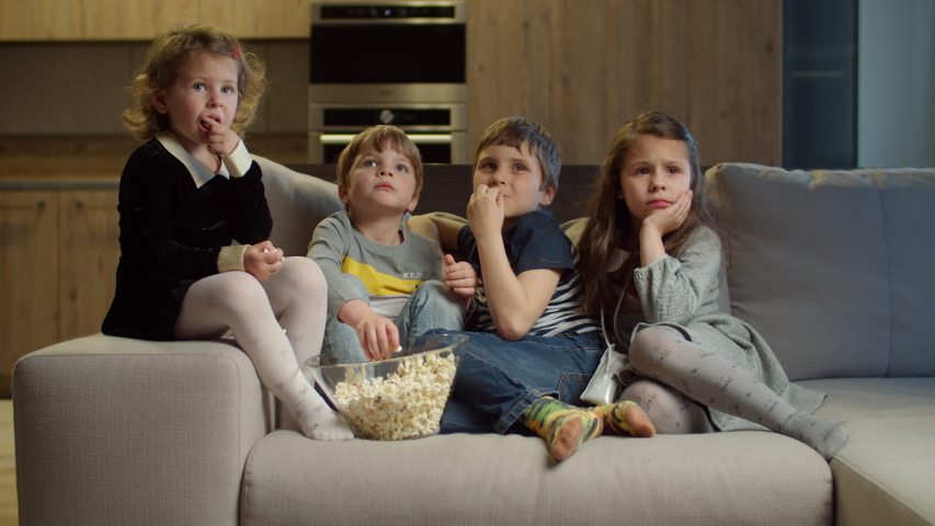 Group of four kids watching TV, eating popcorn sitting on couch at home. Two girls and two boys watching exciting movie at home. Siblings on couch.  | Shutterstock HD Video #1052818769