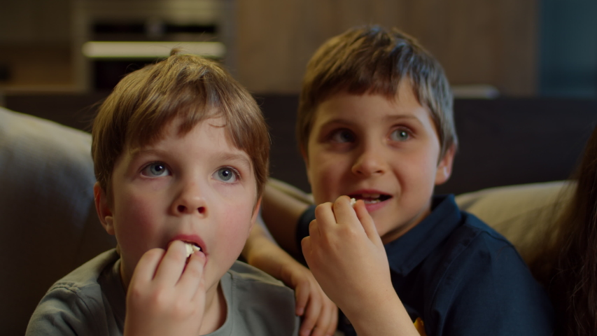 Two brothers watching TV, eating popcorn sitting on couch at home. Two boys watching exciting movie at home. Siblings on couch.