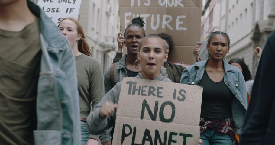 Group of protestors marching on the streets with signs and chanting. Activists protesting against pollution and global warming.  | Shutterstock HD Video #1052821634