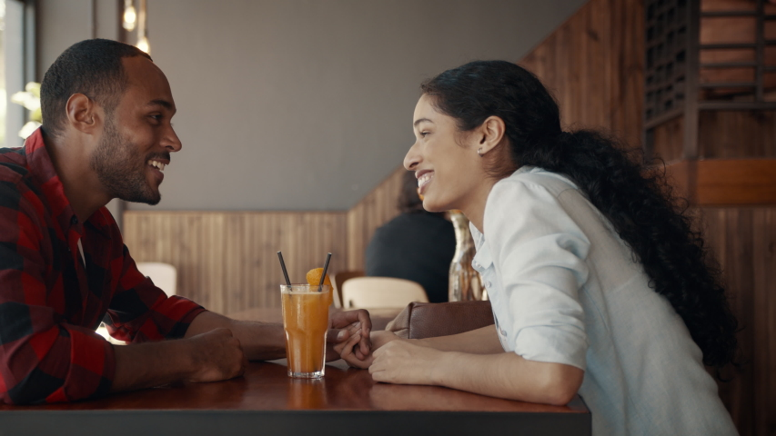 Loving young couple drinking juice from one glass at a cafe and smiling. African man and woman enjoying together on a date.