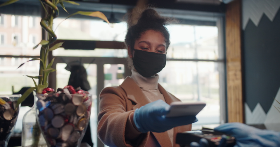 Customer black woman paying for coffee using NFC technology with phone and credit card, contactless payment with student girl woman after coronavirus quarantine pandemic.