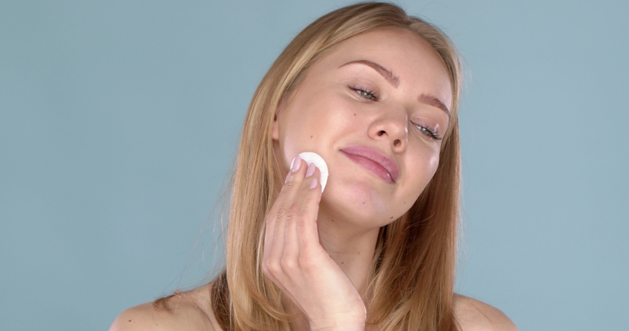 Skin care concept. Woman removing face makeup with cotton swab pad. Facial closeup of beautiful caucasian model with perfect skin. Girl isolated on blue studio background Royalty-Free Stock Footage #1052822567