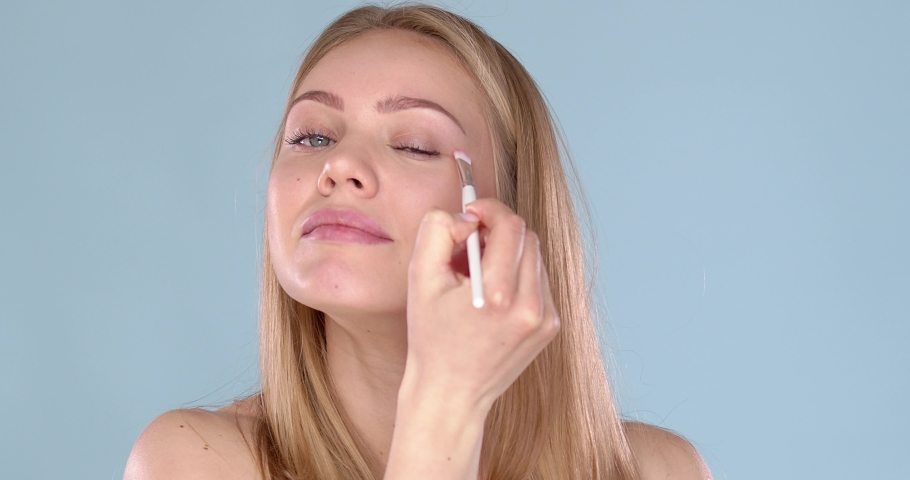 Relaxed and happy caucasian woman applying makeup on her eyes using brush. Isolated on blue background. Slow motion video in studio | Shutterstock HD Video #1052822576