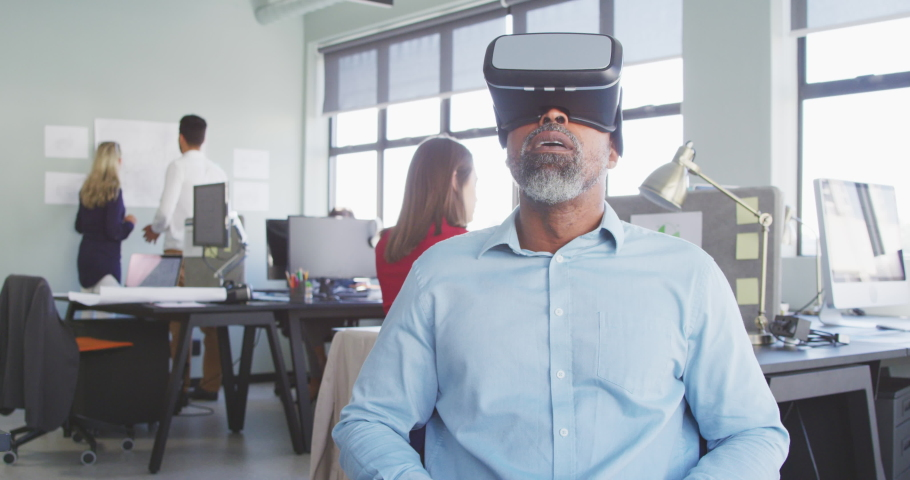 Front view of an African American male business creative working in a casual modern office, sitting and using a VR headset with colleagues in the background in slow motion | Shutterstock HD Video #1052822714