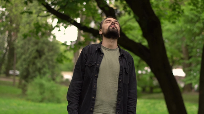 Young bearded caucasian man stands in a park between trees and hands up enjoying nature | Shutterstock HD Video #1052824106