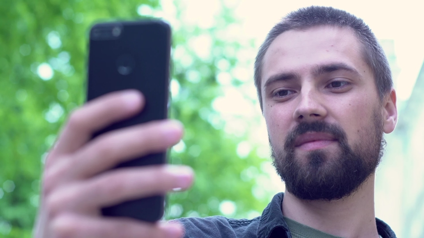 A young caucasian man with a beard holds a phone on his hand and talks. The blogger communicates by video call. The guy smiles on the city street. Close up portrait. | Shutterstock HD Video #1052824145