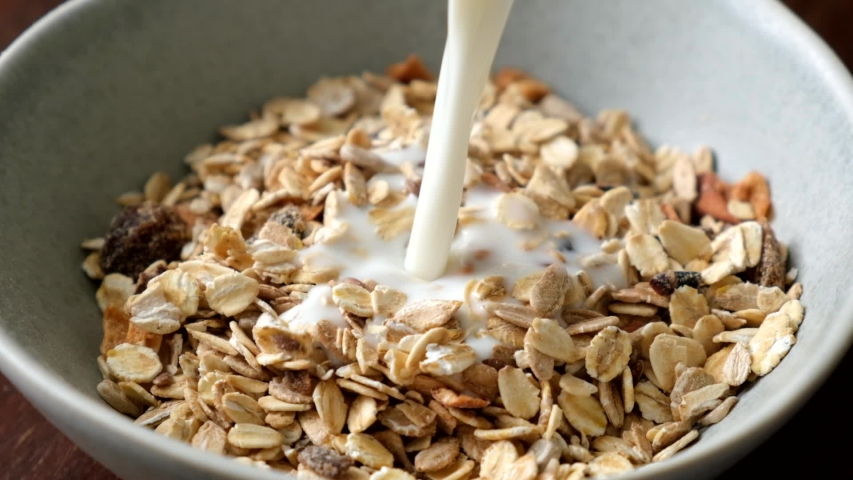 Slow motion milk pouring in bowl of muesli breakfast cereals. Healthy food | Shutterstock HD Video #1052825021