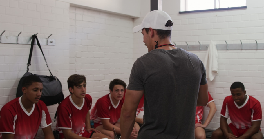 Rear view of a Caucasian male rugby coach standing in the changing room talking to a teenage multi-ethnic male team of rugby players wearing their team strip, sitting and listening