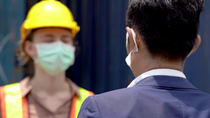 Factory worker in mask face and using measures temperature check body temperature at workplaces with a thermometer during a virus pandemic COVID-19. And man worker going pass inside factory. | Shutterstock HD Video #1052837387