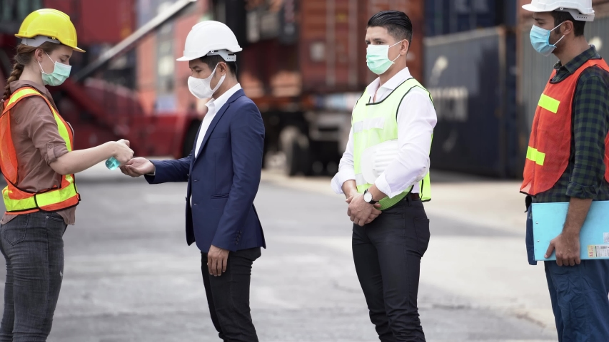 Factory woman worker in a face medical mask and safety dress using alcohol gel for hand cleaning to protect coronavirus disease at outdoor factory warehouse at worker people standing on queue. | Shutterstock HD Video #1052837393
