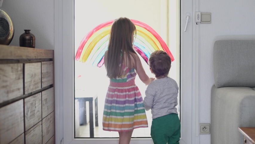 Brother and sister draw a rainbow on the window during quarantine pandemic coronavirus. | Shutterstock HD Video #1052840249