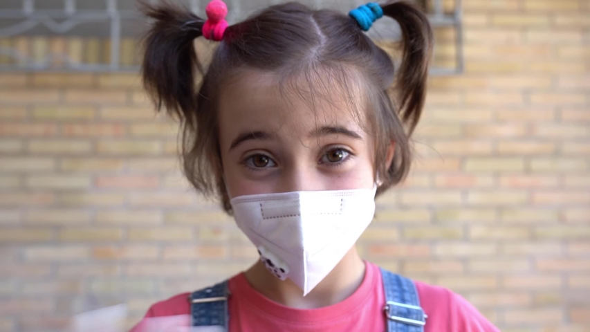 Happy Child girl wearing a protection mask against coronavirus during Covid-19 pandemic. KN95 mask. | Shutterstock HD Video #1052840333