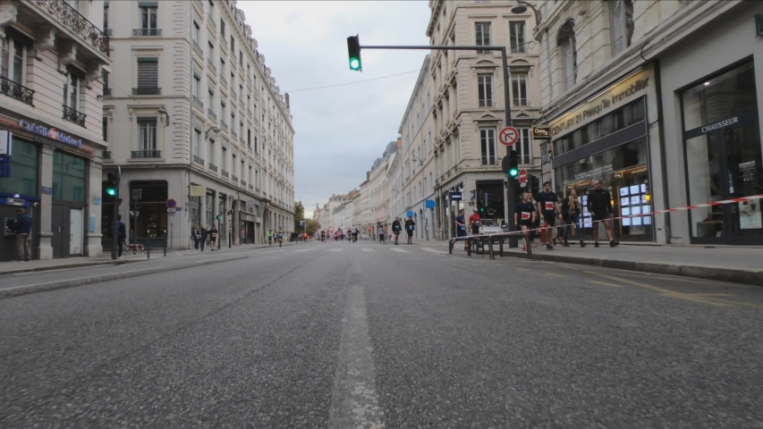 Lyon / France - October 6, 2019: DOLLY SHOT SLOW MOTION -  Rue Antoine de Saint-Exupéry street. Run In Lyon 2019 Finish Line at the Place Bellecour in the background.  | Shutterstock HD Video #1052841026
