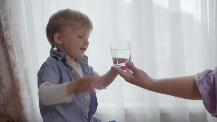 Caring mother gives her healthy male child a glass cup of clean drinking water, thirsty boy drinks pure cool water while sitting against window