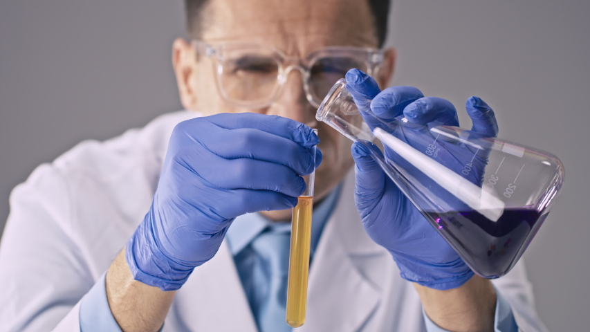 Close up view of male researcher adds purple fluid to test tube with yellow liquid observes component interactions and color changes performing science experiment. Laboratory equipment and glassware | Shutterstock HD Video #1052842190