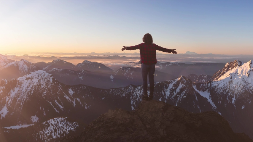 Fantasy Adventure Composite with a Girl on top of a Rock Cliff with Beautiful Canadian Mountain Nature Landscape in Background during Sunset or Sunrise. 2.5D Parallax