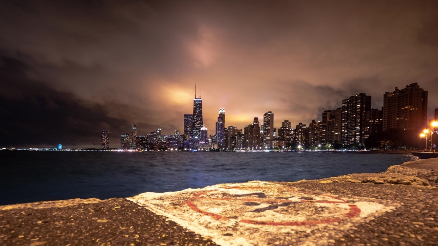 Beautiful panning up skyline cityscape timelapse of Chicago with white worn no diving sign painted on the concrete pavement in foreground and heavy cloud cover lit up from building and city lights.