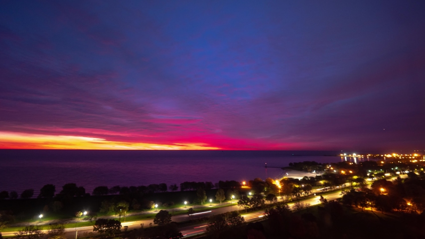 A beautiful zoom out aerial sunrise time lapse with sky on fire pink, yellow, blue, purple, orange and red eruption of color on the clouds as traffic builds on Lake Shore Drive below in Chicago.