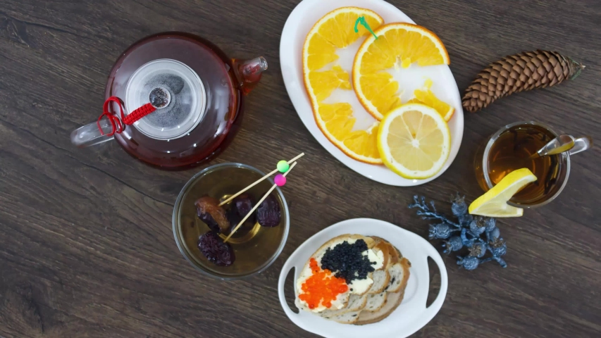 Tea kettle with black tea and sea food caviar on table background. | Shutterstock HD Video #1052850527