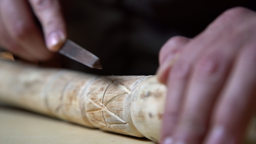 Close up process of man making wooden walking stick indoors during quarantine. Carving wood stick on the table using knife  | Shutterstock HD Video #1052852063