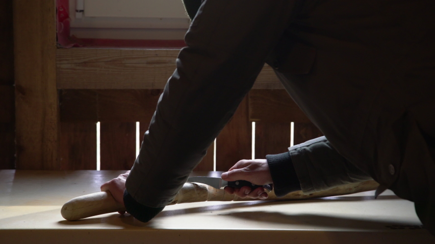 Close up process of man making wooden walking stick indoors during quarantine. Carving wood stick on the table using knife  | Shutterstock HD Video #1052852069