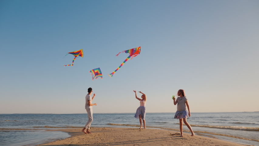 A happy young family with a child play kites together on the beach. Summer holidays Royalty-Free Stock Footage #1052852198
