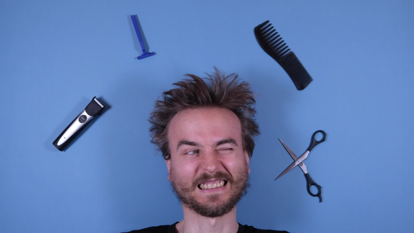 Stop motion animation funny face of bearded disheveled shaggy man and barber grooming hairdresser tools accessories on blue background. Barber shop, hairdresser, cutting hair at home. Royalty-Free Stock Footage #1052852525