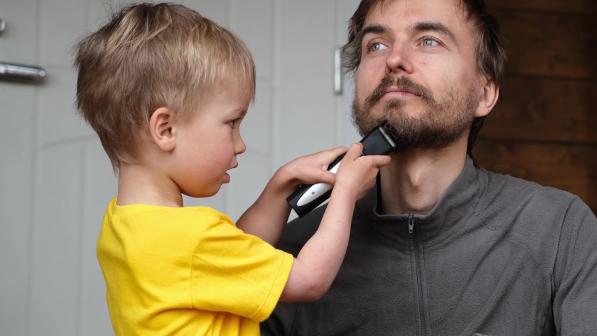 Little child boy cut father beard with clipper. Family haircut, hygiene, beauty and selfcare at home during quarantine lockdown, lifestyle concept. | Shutterstock HD Video #1052852543