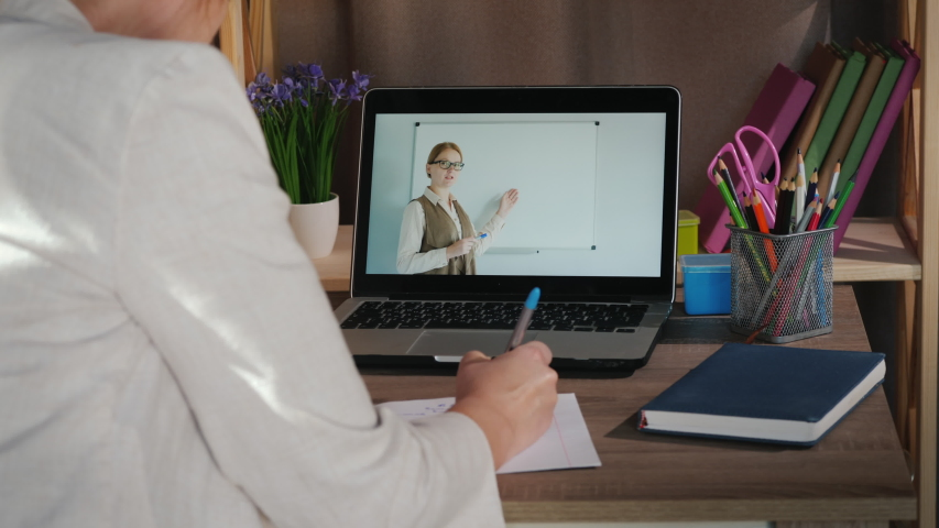 Female student studies at home near laptop, university online concept Royalty-Free Stock Footage #1052855876