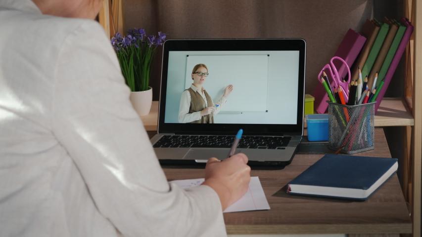 Female student studies at home near laptop, university online concept #1052855876