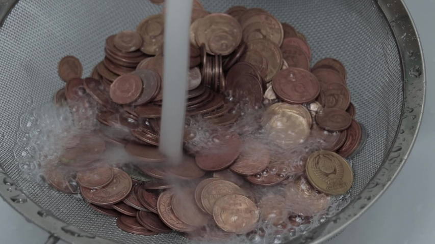 Money laundering concept, coins under tap water | Shutterstock HD Video #1052856083