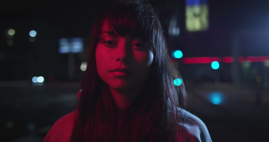 Young trendy ambitious woman looking intense in the camera at night next to neon light. Nightlife youth and urban atmosphere of girl looking to camera. Shot on RED. | Shutterstock HD Video #1052858990