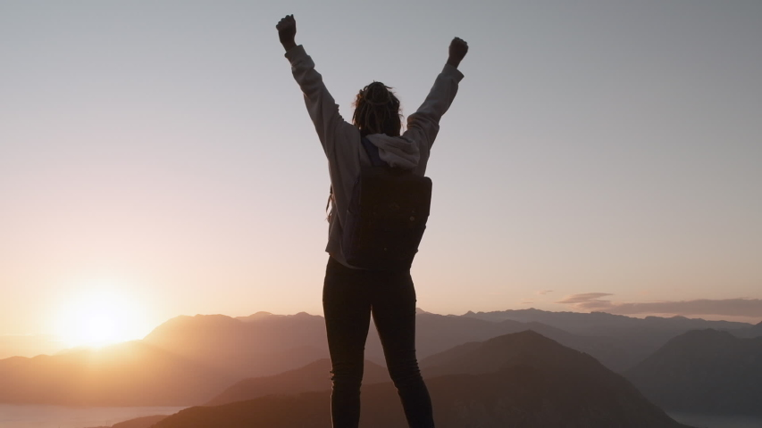 Young inspired Dreadlocks woman raises her hands up standing on the top of a mountain above the sea against beautiful sunrise sky. Watching the sunset with beautiful landscape in Montenegro.  Royalty-Free Stock Footage #1052859839