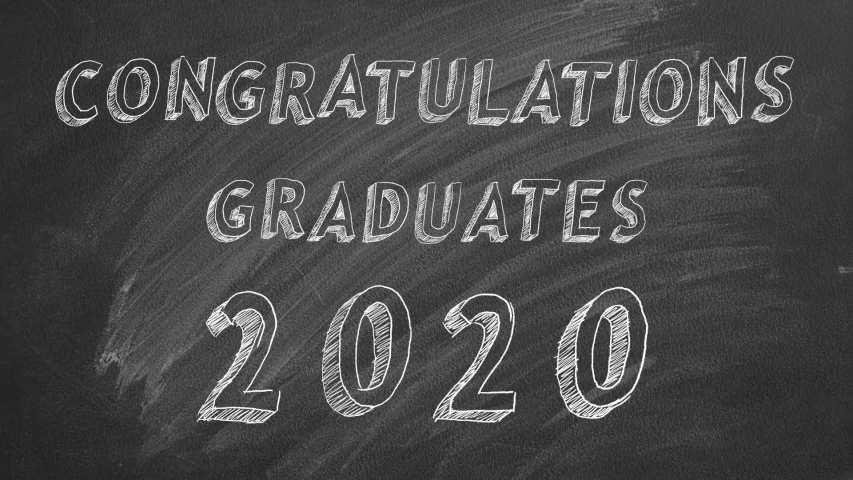 "Hand drawing text ""Congratulations graduates.  2020."" and graduation caps   on blackboard. 