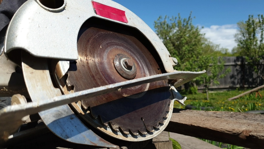 A man saws a Board with an electric circular saw, close-up   Shutterstock HD Video #1052861525