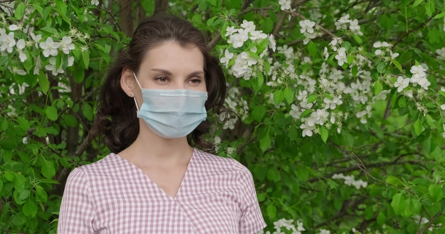 Girl removes medical mask on nature near tree and takes breath. Young woman takes off on mask. Slow motion shooting, concept. Person wears face mask then removes face mask and smelling flowering tree | Shutterstock HD Video #1052865554