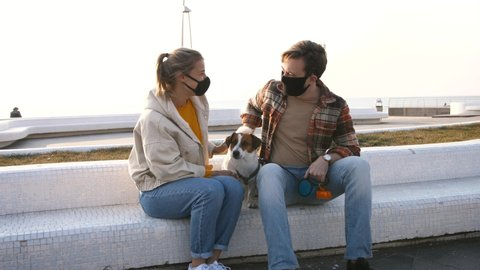 Young happy couple in protective medical masks sitting and petting cute Jack Russel terrier dog outdoors near the sea