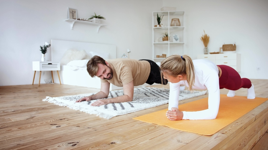 Young couple is doing plank plank exercise at home in cozy bright bedroom, slow motion. Stay at home concept | Shutterstock HD Video #1052865905