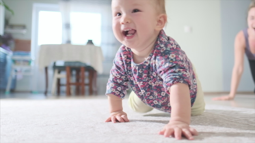 Happy baby crawls in the room. Infant baby plays with family in the house and learns how to crawl quickly during catch up games