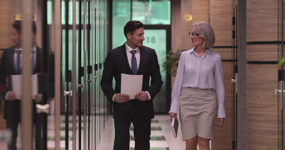Confident male manager in formal wear walking in corridor with pleasant middle aged 60s female company boss leader, discussing working issues or enjoying pleasant informal conversation in office. Royalty-Free Stock Footage #1052867048