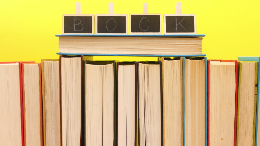 Title books appear on the ordered books on yellow background - Stop motion   Shutterstock HD Video #1052867663