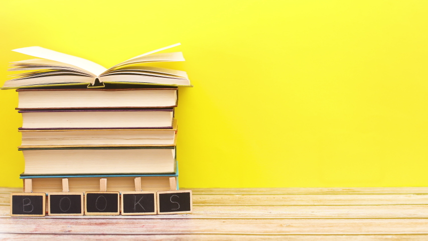 Title books appear in front of pile of books with opened the last book - Stop motion    Shutterstock HD Video #1052867672