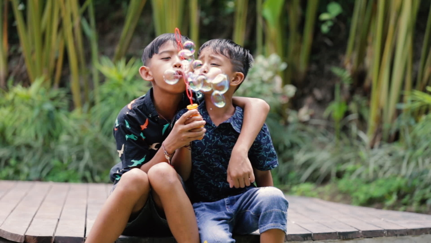 Cute little boys are blowing a soap bubbles outside. Indonesian or malaysian brother siblings are playing together outdoors | Shutterstock HD Video #1052869043
