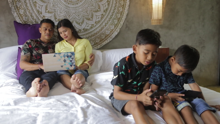 Indonesian or malaysian family addicted to digital technology. Family in bed using smartphones. Mom, dad and children obsessed with devices overusing social media, playing games or watching videos | Shutterstock HD Video #1052869052