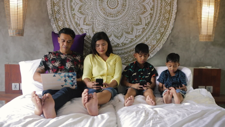Indonesian or malaysian family addicted to digital technology. Family in bed using smartphones. Mom, dad and children obsessed with devices overusing social media, playing games or watching videos | Shutterstock HD Video #1052869055
