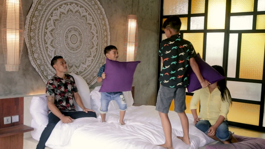 Southeast Asian family spending time at home. Indonesian or malaysian parents and children in bedroom playing having fun together | Shutterstock HD Video #1052869067