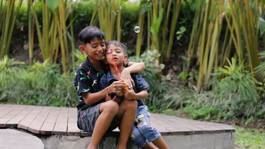 Cute little boys are blowing a soap bubbles outside. Indonesian or malaysian brother siblings are playing together outdoors | Shutterstock HD Video #1052869076